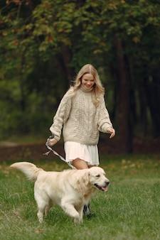 Mujer con un suéter marrón. dama con un labrador