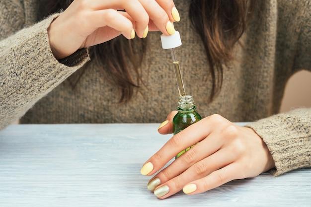 Mujer en un suéter marrón con la manicura amarilla que sostiene una botella verde con el aceite cosmético, primer