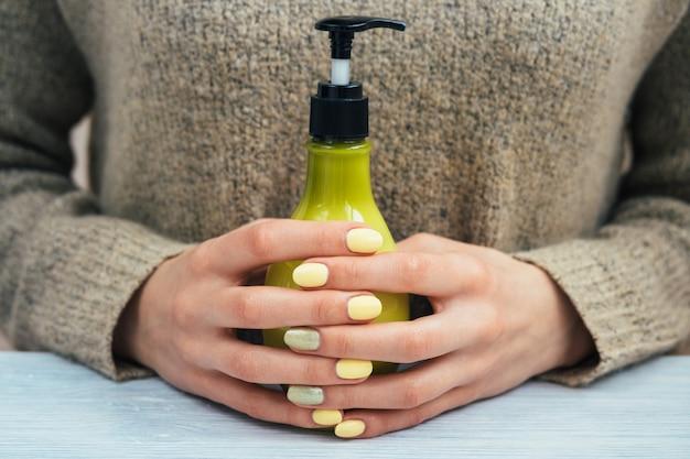 Mujer en suéter marrón con manicura amarilla sosteniendo una botella verde con cosméticos, de cerca