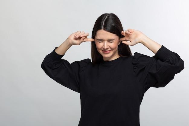 Mujer en suéter negro cierra sus oídos