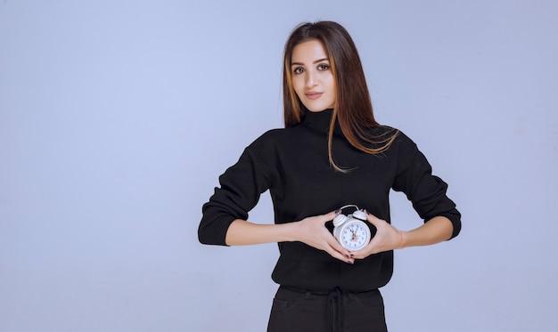 Mujer de suéter negro sosteniendo el despertador.