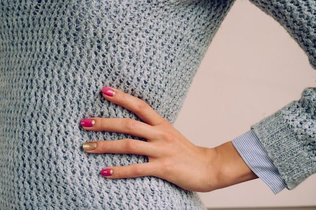 Una mujer en un suéter de punto gris se puso la mano en la cintura. sobre las uñas manicura rosa y dorada.