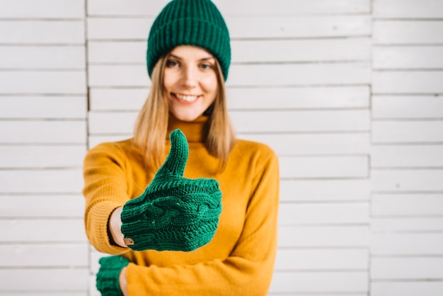 Mujer en suéter que muestra el pulgar hacia arriba