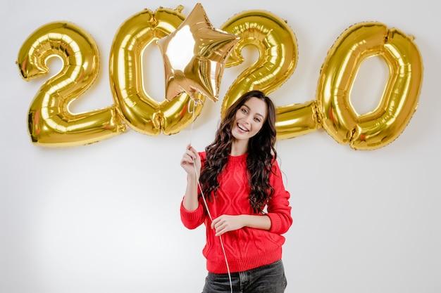 Mujer en suéter rojo con globo de estrella dorada frente a 2020 globos de año nuevo