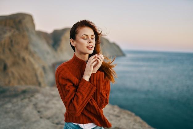 Mujer con un suéter rojo en las montañas cerca del modelo de turismo de viajes por mar