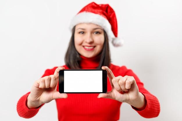 Mujer en un suéter rojo y sombrero de navidad muestra un teléfono inteligente con una pantalla en blanco en blanco