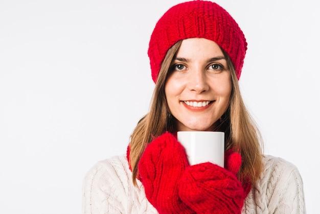 Mujer en suéter sosteniendo la taza blanca