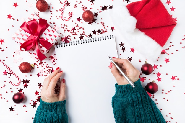 Mujer en suéter verde escribiendo lista de verificación de planes y sueños para el próximo año. lista de deseos para navidad. lista de tareas para el nuevo año 2020 con decoración roja de vacaciones.