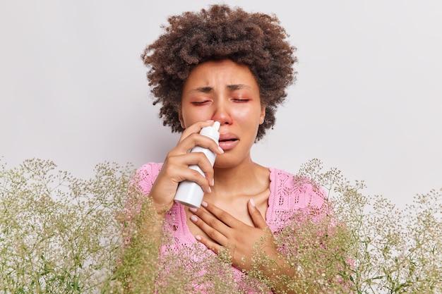 La mujer sufre de secreción nasal usa un aerosol nasal tiene ojos rojos hinchados tiene una reacción de rinitis alérgica en poses de plantas silvestres en blanco