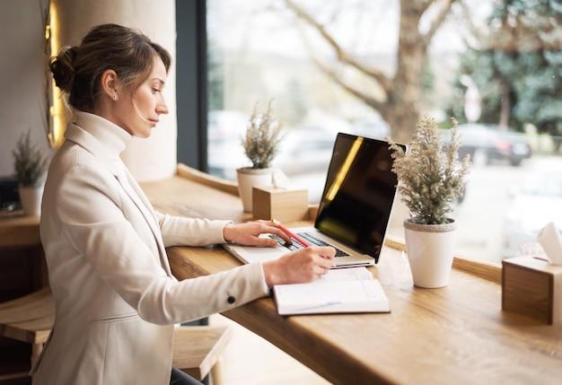Mujer en la suite blanca que trabaja en la computadora portátil en el almuerzo de negocios