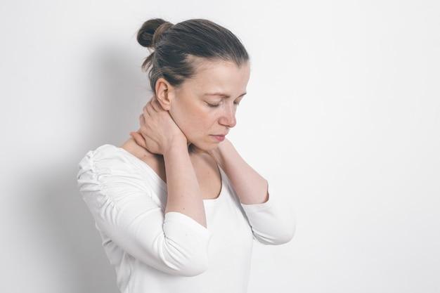 Una mujer sujeta su mano por el cuello. dolor de la columna vertebral. fatiga.