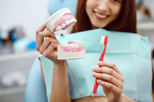 Mujer sujetando un cepillo de dientes y un molde dental