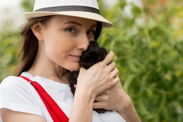 Mujer sujetando un conejo negro