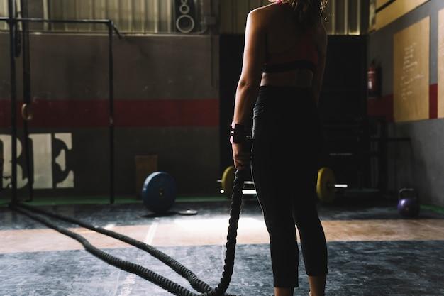 Mujer sujetando cuerda en gimnasio