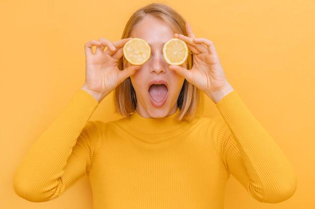 Mujer sujetando limones enfrente de sus ojos en un escenario amarillo