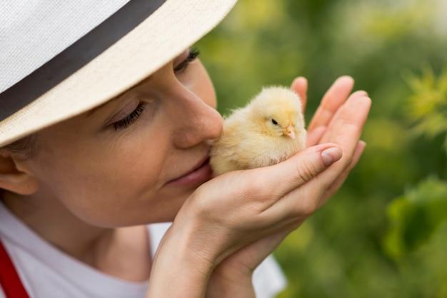 Mujer sujetando un pollo en una granja