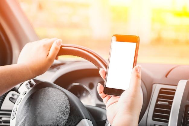 Mujer sujetando un teléfono al atardecer mientras conduce