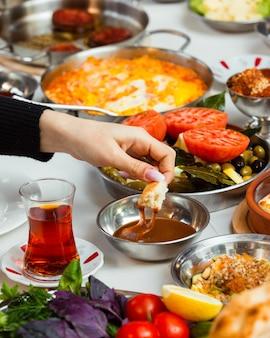 Mujer sumergiendo pan en miel servido para el desayuno turco