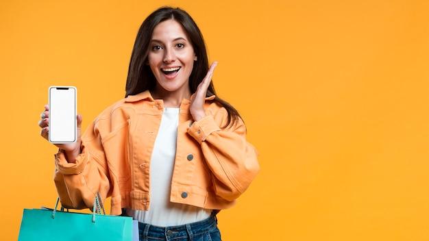 Mujer super emocionada sosteniendo smartphone y bolsas de compras