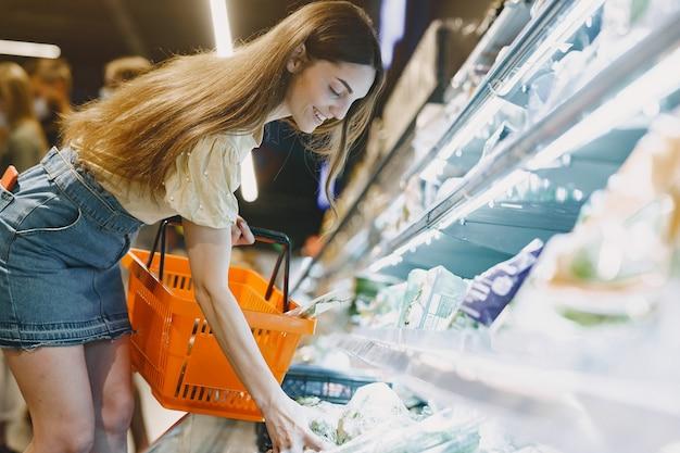 Mujer en el supermercado. mujer con camiseta marrón. la gente elige productos.