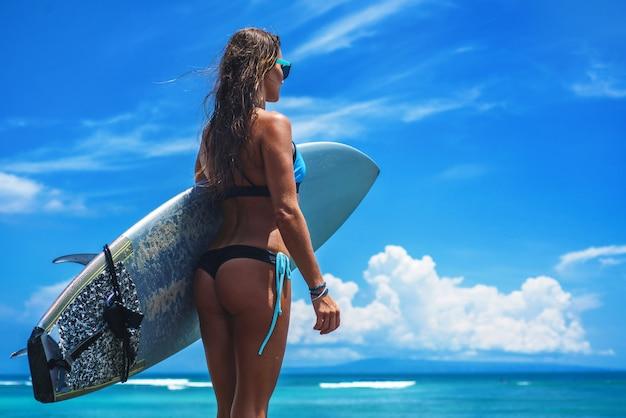 Mujer surfista vistiendo bikinis y gafas con un tablero azul contra el océano y el cielo azul con nubes
