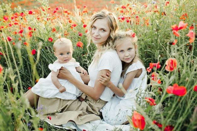 Mujer con sus dos hijas se agacha en campo de amapolas
