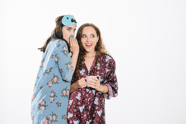 Mujer susurrando en la oreja de su amiga sobre fondo blanco