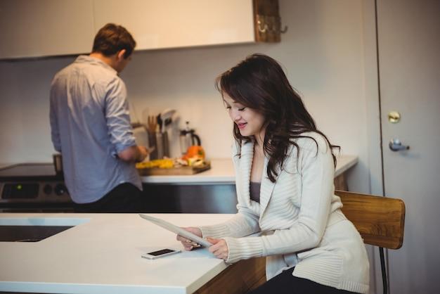 Mujer con tableta digital mientras el hombre trabaja en segundo plano.