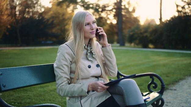 Mujer con tableta y teléfono móvil sentado en el banco del parque.
