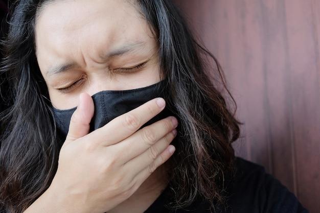 Mujer tailandesa asiática con una máscara de tela negra para prevenir el virus covid-19 o corona y la enfermedad epidémica
