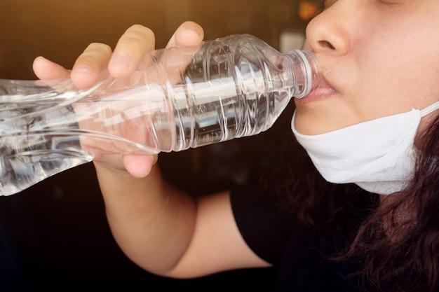 Mujer tailandesa asiática que usa una máscara de tela blanca para prevenir el virus covid-19 o corona y el valor de contaminación del aire pm 2.5 en tailandia y bebe agua mineral embotellada. concepto de salud y enfermedad