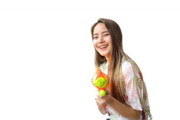 Una mujer tailandesa hermosa que sonríe fresca y feliz, en su mano que sostiene un arma de agua en el festival tailandés de songkran en un fondo blanco.