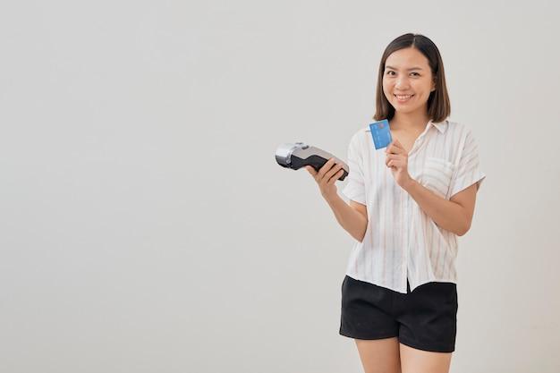 Mujer tailandesa presentando tarjeta de crédito para realizar el pago