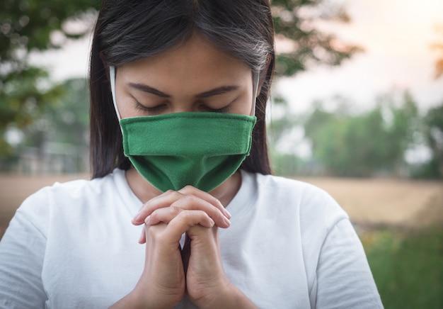 Mujer tailandesa que usa una máscara para proteger el virus, covid 19 orando por las bendiciones de dios para que el mundo esté a salvo de esta epidemia.