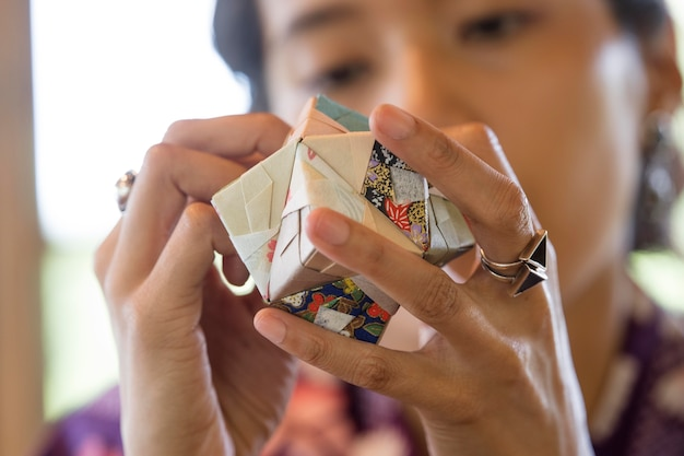 Mujer talentosa haciendo origami con papel japonés