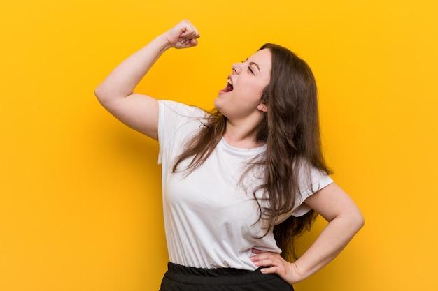Mujer de talla grande con curvas joven que levanta el puño después de una victoria, concepto ganador.