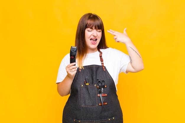 Mujer de talla grande que parece infeliz y estresada, gesto de suicidio haciendo un signo de pistola con la mano, apuntando a la cabeza