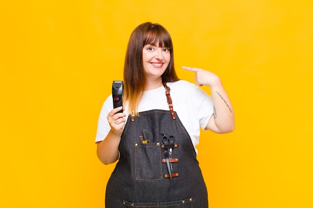 Mujer de talla grande sonriendo con confianza apuntando a su propia sonrisa amplia, actitud positiva, relajada y satisfecha