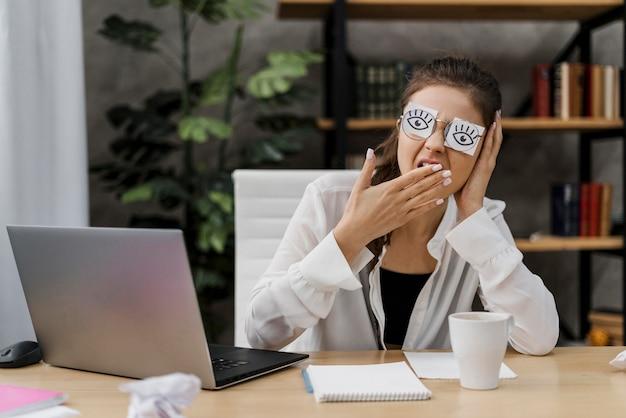 Mujer tapándose los ojos con ojos dibujados en papel