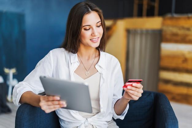 Mujer con tarjeta bancaria para pagar productos comprados en línea.