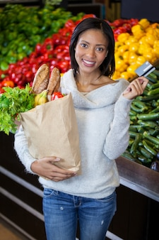 Mujer con tarjeta de crédito y bolsa de supermercado