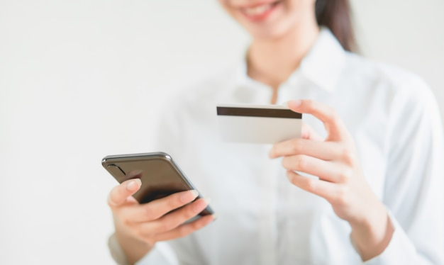 Mujer con tarjeta de crédito con compras en línea en el teléfono inteligente e ingrese el código de pago del producto en la oficina en casa.