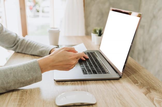 Mujer con tarjeta de crédito en la computadora portátil para comprar en línea