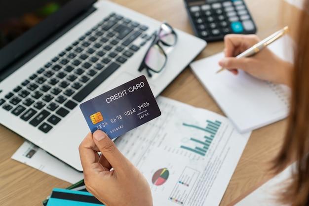Mujer con tarjeta de crédito y escritura, cuenta y concepto de ahorro.
