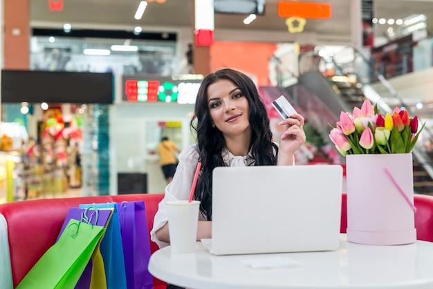 Mujer con tarjeta de crédito y portátil en la cafetería haciendo compras