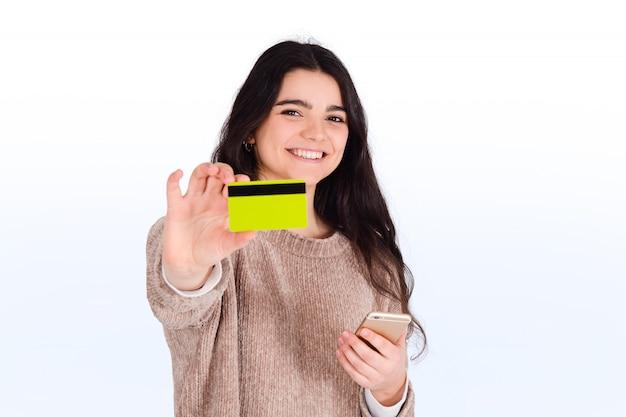 Mujer con tarjeta de crédito y teléfono inteligente.