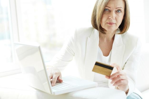 Mujer con tarjeta y portátil para comprar en línea
