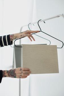 Mujer tatuada colgando maqueta de libros en una percha
