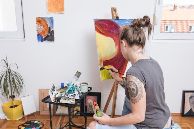 Mujer tatuada que pinta imagen colorida sobre lienzo.