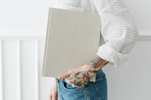 Mujer tatuada sosteniendo una maqueta de libro